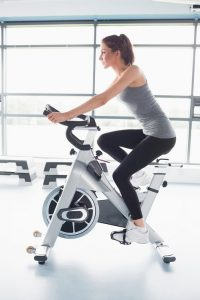 Young woman using an upright exercise bike
