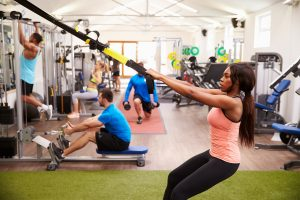 People using exercise equipment in a busy gym